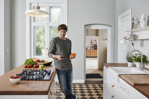 Man using smartphone and holding bell pepper in kitchen - RORF01138