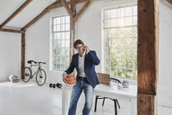 Smiling businessman with basketball on cell phone in penthouse - RORF01141