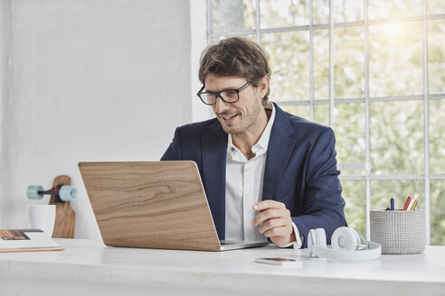 Smiling businessman using laptop on desk - RORF01147