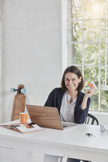 Smiling businesswoman using laptop on desk holding card - RORF01153