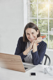 Portrait of smiling businesswoman with laptop on desk holding card - RORF01156