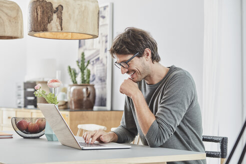 Smiling man using laptop on table at home - RORF01162