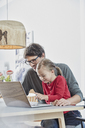 Smiling father and daughter using laptop on table at home - RORF01171