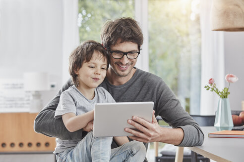 Happy father and son using tablet at home together - RORF01177