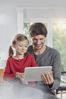 Smiling father and daughter using tablet at home together - RORF01180