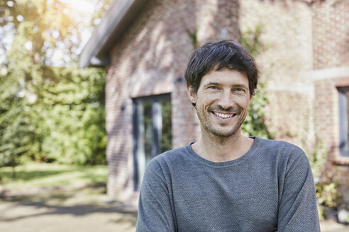 Portrait of smiling man in front of his home - RORF01189