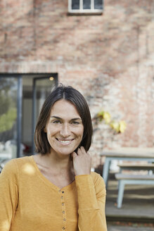 Portrait of smiling woman in front of her home - RORF01192