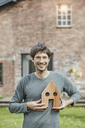 Portrait of smiling man in front of his home holding house model - RORF01198