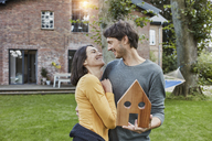 Happy couple in garden of their home holding house model - RORF01204
