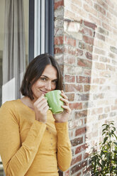 Portrait of smiling woman drinking from cup in front of her home - RORF01213
