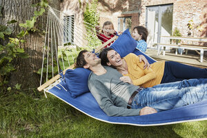 Happy family playing in hammock in garden of their home - RORF01216