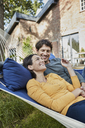 Happy couple lying in hammock in garden of their home - RORF01219