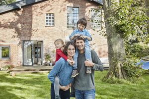 Portrait of happy family in garden of their home - RORF01228