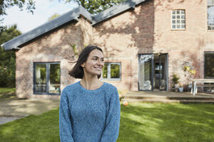 Smiling woman in garden of her home - RORF01231