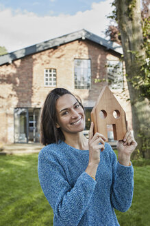Portrait of smiling woman in garden of her home holding house model - RORF01237