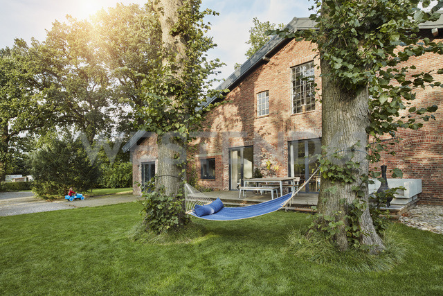 Residential house with hammock in garden and girl playing in background - RORF01240
