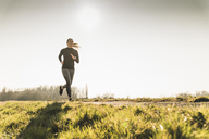 Young woman running on rural path - UUF13047