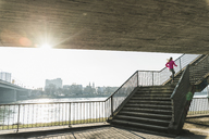 Young woman running up stairs at a river - UUF13053