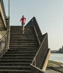 Young woman running up stairs at a river - UUF13056