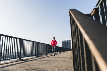 Young woman running on bridge in the city - UUF13062