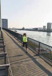 Young woman running on bridge at the riverside - UUF13065