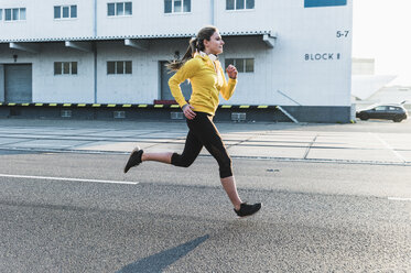 Young woman running on a street - UUF13074