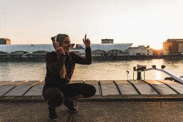 Happy sportive young woman listening to music at the riverside in the city at sunset - UUF13083