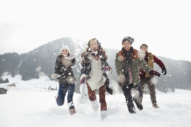Happy friends playing in snowy field - CAIF12346
