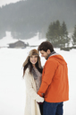 Happy couple holding hands in snowy field - CAIF12355