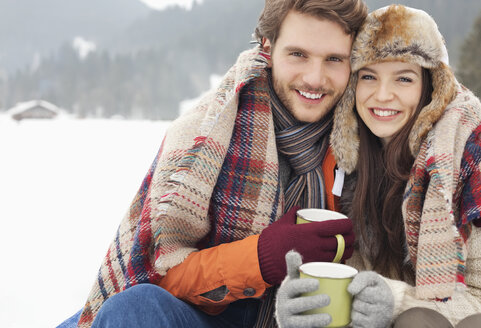 Portrait of happy couple drinking coffee in snowy field - CAIF12358