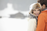 Portrait of smiling woman hugging man in snowy field - CAIF12367