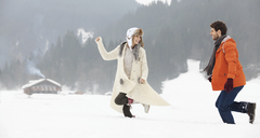 Couple running in snowy field - CAIF12370