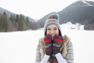 Portrait of enthusiastic woman wearing knit hat and gloves in snowy field - CAIF12373