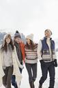 Happy friends walking in snowy field - CAIF12376