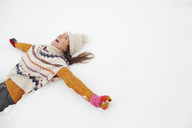 Enthusiastic woman making snow angel - CAIF12379