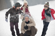 Playful family enjoying snowball fight in field - CAIF12391
