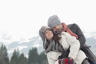 Happy couple hugging with mountains in background - CAIF12394