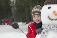 Close up of smiling boy behind snowman - CAIF12406