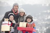 Portrait of happy family with Christmas gifts in snow - CAIF12412