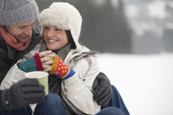 Happy couple drinking coffee in snow - CAIF12415