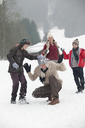 Happy family enjoying snowball fight in field - CAIF12427