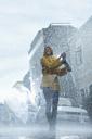 Happy woman walking barefoot in rain - CAIF12436