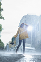 Woman in raincoat carrying wellingtons and walking barefoot in rain - CAIF12442