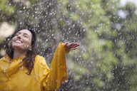 Happy woman standing with arms outstretched in rain - CAIF12448