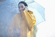 Happy woman talking on cell phone under umbrella in rain - CAIF12451
