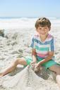Boy building sandcastle on beach - CAIF12457