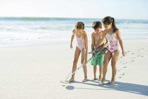 Children using metal detector on beach - CAIF12460