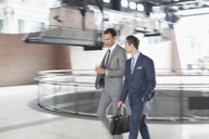 Corporate businessmen with coffee walking and talking - CAIF12478