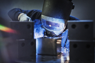 Welder using welding torch on part in steel factory - CAIF12496