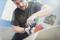 Worker using sander in steel factory - CAIF12508